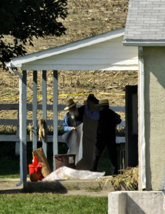 Men work outside West Nickel Mines Amish School Tuesday, Oct. 3, 2006, the day after a gunman killed several children at the school in Nickel Mines, Pa. A man who laid siege to the one-room Amish schoolhouse told his wife he had molested young children decades ago and left a note saying he had