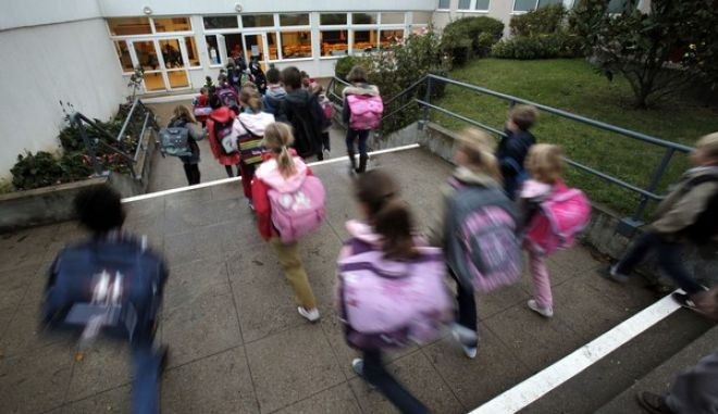 FILE - In this Oct. 5, 2012 file photo, students enter school of La Ronce in Ville d'Avray, west of Paris. France's government has unveiled Wednesday Aug. 24, 2016 a plan to teach children how to react in case of an attack at school. Every school will have to organize three security drills per year, including one based on the scenario of an attack with at least one assailant inside the building. (AP Photo/Christophe Ena)