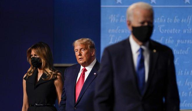 Ο Τζο Μπάιντεν και στο βάθος το ζεύγος Τραμπ