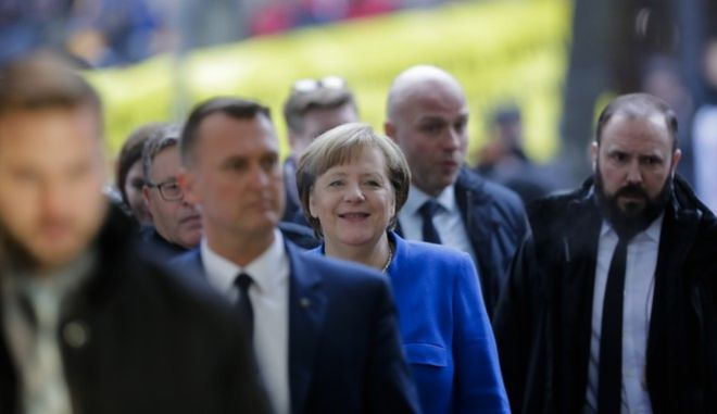 Surrounded by security guards German Chancellor Angela Merkel, center, arrives for exploratory talks about a new German government between her Christian Unions block and the Social Democratic Party at the SPD headquarters in Berlin, Thursday, Jan. 11, 2018. (AP Photo/Markus Schreiber)