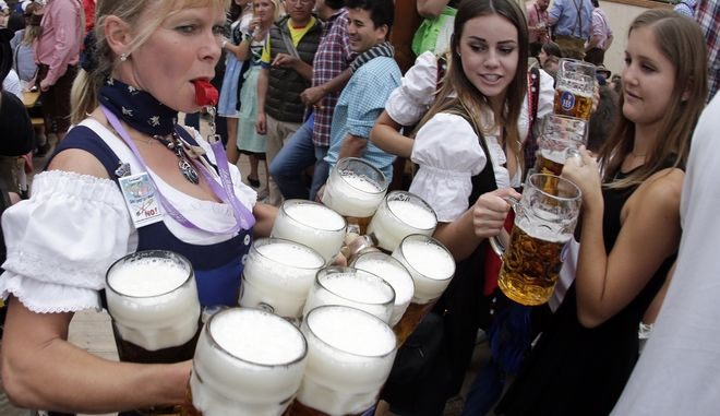 A waitress carries beer mugs during the opening of the 181st Oktoberfest beer festival in Munich, southern Germany, Saturday, Sept. 20, 2014. The world's largest beer festival will be held from Sept. 20 to Oct. 5, 2014. (AP Photo/Matthias Schrader)