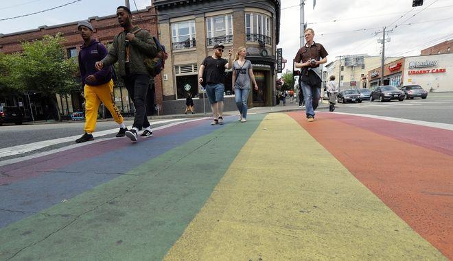 Περαστικοί διασχίζουν δρόμο βαμμένο στα χρώματα του ουράνιου τόξου