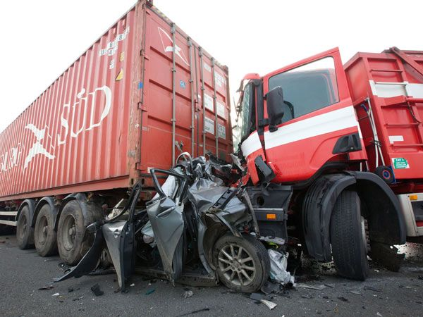 A car is seen crushed between two trucks during a pileup on a main motorway in Zonnebeke, Belgium on Tuesday, Dec. 3, 2013. Nearly 100 cars and trucks were involved in three pile-ups at a highway in western Belgium in a dense morning fog Thursday, leaving at least one dead and 54 injured. (AP Photo/Kurt Desplenter) BELGIUM OUT