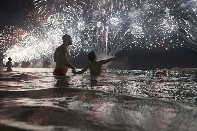 People watch the fireworks exploding over Copacabana beach during the New Year's celebrations in Rio de Janeiro, Brazil, Monday, Jan. 1, 2018. (AP Photo/Leo Correa)