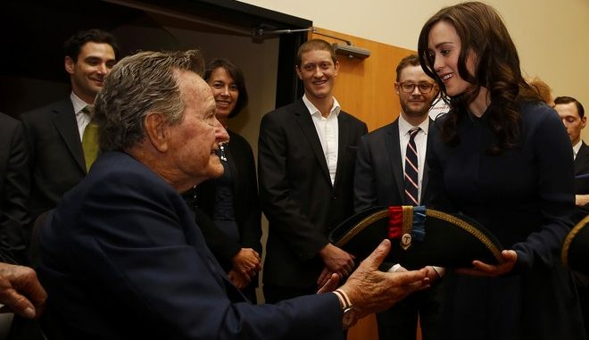 IMAGE DISTRIBUTED FOR AMC - Former President George H.W. Bush, left, receives a tri-corner hat from actress Heather Lind, right, at a private screening of AMC's new series TURN on Saturday, March, 29, 2014 in Houston, Texas. (Photo by Aaron M. Sprecher/Invision for AMC/AP Images)