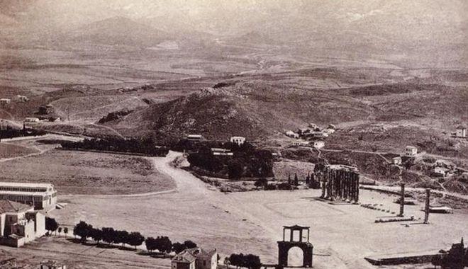 (Φωτογραφία του 1870- Οι στύλοι του Ολυμπίου Διός είναι έξω από την τότε μικρή πόλη. Χωράφια και αδιαμόρφωτοι δρόμοι περιβάλλουν τα αρχαία ερείπια. Η σημερινή λεωφόρος που οδηγεί στη Συγγρού, δεν ήταν παρά ένας καρόδρομος)