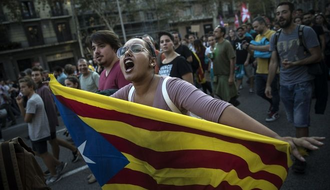 A woman carries an independence Catalan flag as demonstrators march downtown Barcelona, Spain, Tuesday Oct. 3, 2017. Thousands of people demonstrated against the confiscation of ballot boxes and charges on unarmed civilians during Sunday's referendum, declared illegal by Spain's Constitutional Court, on Catalonia's secession from Spain.(AP Photo/Santi Palacios)