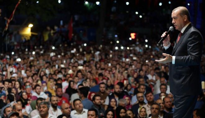 Turkey's President Recep Tayyip Erdogan addresses his supporters gathered in front of his residence in Istanbul, early Tuesday, July 19, 2016. Turkey's Interior Ministry has fired nearly 9,000 police officers, bureaucrats and others and detained thousands of suspected plotters following a foiled coup against the government, Turkey's state-run news agency reported Monday. (AP Photo/Murat Cetinmuhurdar, Presidential Press Service, Pool)