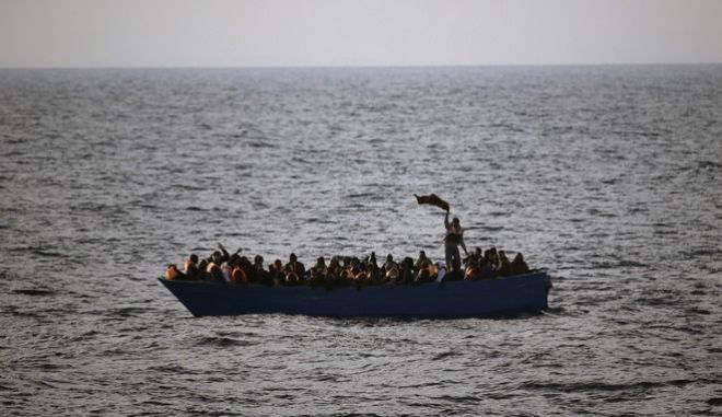 FILE- In this Friday, Feb. 3, 2017 file photo, migrants and refugees wave for help from inside a wooden boat 21 miles north of Sabratha, Libya. The chief of the European border and coast guard agency says migrant deaths in the Mediterranean on the Libya-to-Italy smuggling route have increased to a record level despite ever more rescue vessels trying to prevent mass drownings. (AP Photo/Emilio Morenatti, File)