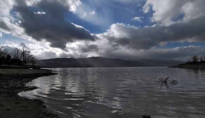 Σύννεφα πάνω από την λίμνη Πλαστήρα με φόντο τις κορυφές των Αγράφων πάνω από το χωριό Νεοχώρι