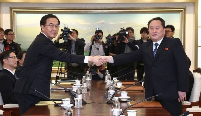 South Korean Unification Minister Cho Myoung-gyon, left, poses with head of North Korean delegation Ri Son Gwon while shaking hands during their meeting at the Panmunjom in the Demilitarized Zone in Paju, South Korea, Tuesday, Jan. 9, 2018. Senior officials from the rival Koreas said Tuesday they would try to achieve a breakthrough in their long-strained ties as they sat for rare talks at the border to discuss how to cooperate in next month's Winter Olympics in the South and other issues. (Korea Pool via AP)