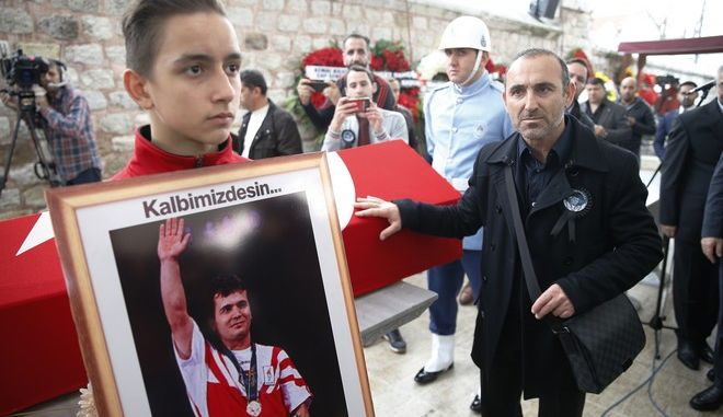 """Valerios Leonidis, right, of Greece, a veteran weightlifter who won the bronze medal in the 1996 Atlanta Olympic Games 59-64kg featherweight men's event, touches the coffin of his friend Turkish weightlifter Naim Suleymanoglu, who won gold at the same event, prior to his funeral procession in Istanbul, Sunday, Nov. 19, 2017. Suleymanoglu, known as """"Pocket Hercules"""" won three straight Olympic gold medals for Turkey between 1988 and 1996. Suleymanoglu was considered one of the sport's greatest athletes and earned his nickname for his strength and diminutive size. He was 50. (AP Photo/Lefteris Pitarakis)"""