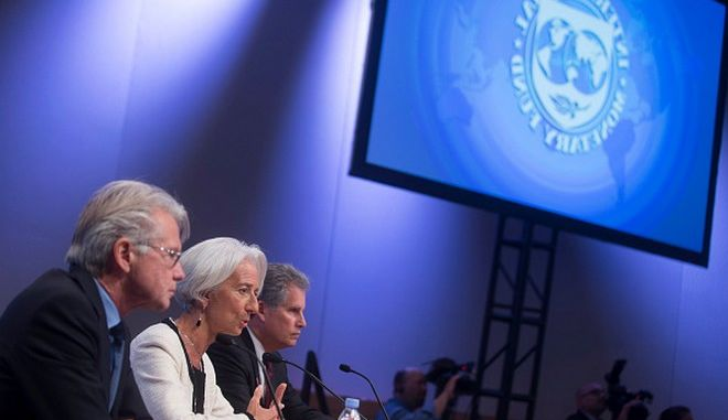 "David Lipton, first deputy managing director of the International Monetary Fund (IMF), from left, Christine Lagarde, managing director of the IMF, and Gerry Rice, director of communications at the IMF, hold a news conference during the IMF and World Bank Group Annual Meetings in Washington, D.C., U.S., on Thursday, Oct. 9, 2014. The global response to the Ebola crisis is ""way behind the curve,"" World Bank President Jim Yong Kim said today, as leaders of the three affected African nations appealed for financing and faster assistance. Photographer: Andrew Harrer/Bloomberg via Getty Images"