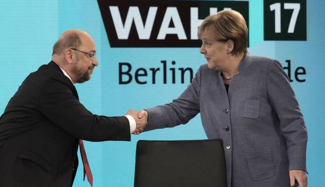 German Chancellor Angela Merkel, head of the Christian Democratic Party CDU, is greeted by her her challenger Martin Schulz, head of the Social Democratic Party SPD, prior to a TV talk of the party leaders in Berlin, Germany, Sunday, Sept. 24, 2017, after the German parliament elections. (AP Photo/Gero Breloer, pool)