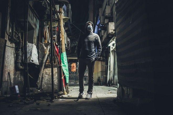 Άντρας με μάσκα προφύλαξης σε υποβαθμισμένη περιοχή πόλης.