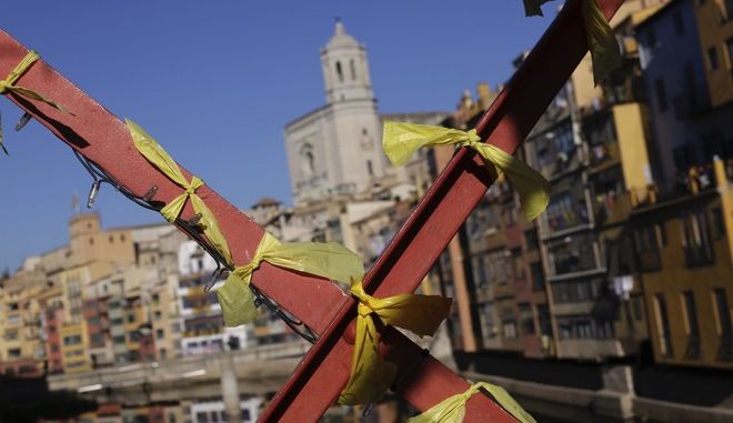 Yellow ribbons decorate a bridge in Girona, Spain, on Thursday, Dec. 21, 2017. The yellow ribbon stands as a symbol of support for imprisoned pro-independence politicians. Catalans are choosing new political leaders in a highly contested election called by central authorities to quell a separatist bid in Spain's northeastern region. (AP Photo/Bernat Armangue)