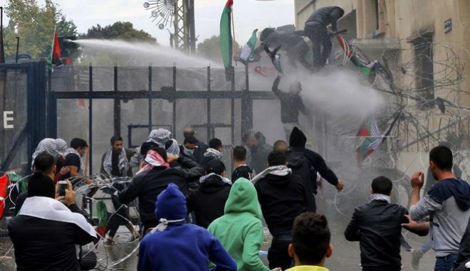 Protesters try to enter the U.S. embassy as they are sprayed by riot police using water cannons during a demonstration in Aukar, east of Beirut, Lebanon, Sunday, Dec. 10, 2017.  A few hundred demonstrators, including Palestinians, pelted security outside the embassy with stones and burned an effigy of U.S. President Donald Trump in a protest to reject Washington's recognition of Jerusalem as capital of Israel. (AP Photo/Bilal Hussein)