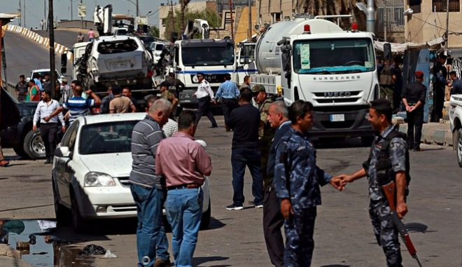 Iraqi security forces secure the site of a car bomb explosion as they prepare to tow away damaged vehicles, in Baghdad, Iraq, Sunday, May 14, 2017. (AP Photo/Khalid Mohammed)