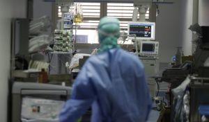 Γιατρός επισκέπτεται ασθενή με κορονοϊό σε ΜΕΘ.