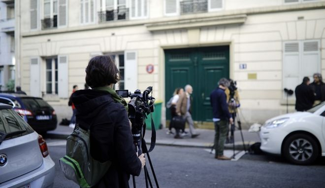 Members of the media stand outside the entrance of an apartment building where police found an explosive device early Saturday, Tuesday, Oct. 3, 2017. Five people are in custody and a terrorism investigation is under way after an apparent failed bombing attempt in a chic Paris neighborhood. (AP Photo/Kamil Zihnioglu)