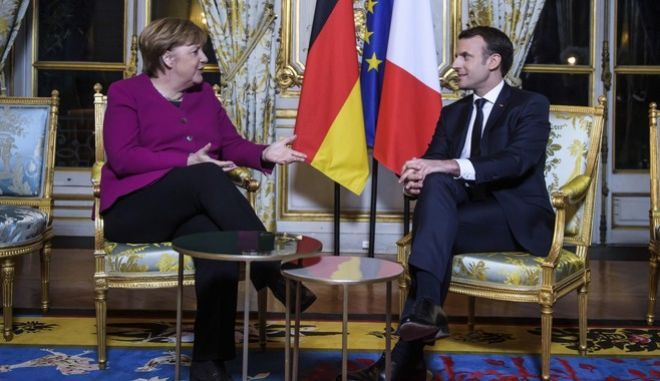 France's President Emmanuel Macron, right, and German Chancellor Angela Merkel, talk during their meeting, at the Elysee Palace, in Paris, Friday, Jan. 19, 2018. (Christophe Petit Tesson, Pool via AP)