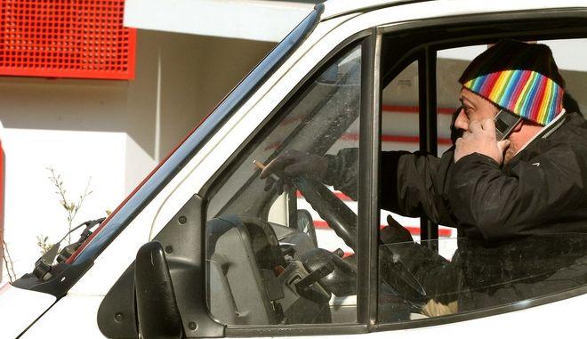 Οδηγός μιλάει στο κινητό του τηλέφωνο
