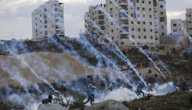 Palestinians run away from teargas during clashes with Israeli troops following protests against U.S. President Donald Trump's decision to recognize Jerusalem as the capital of Israel, in the West Bank city of Ramallah, Sunday, Dec. 10, 2017. (AP Photo/Nasser Shiyoukhi)