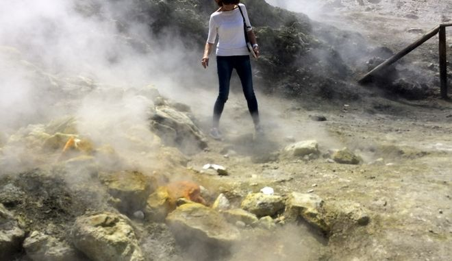 In this photo taken on Saturday, April 30, 2016, a woman takes a close look at a steaming fumarola at the Solfatara crater bed, in the Phlegraean Fields near Naples, Italy. Fields -- Campi Flegrei in Italian -- are a sprawling constellation of ancient volcanic centers. (AP Photo/Frances D'Emilio)