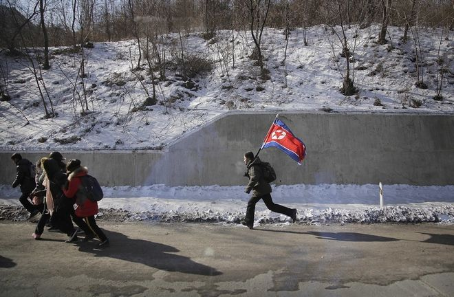 In this Saturday, Feb. 11, 2017, photo, a boy runs with the national flag along the Pyongyang-Wonsan highway in North Korea. Wonsan, about 200 kilometers (125 miles) from the capital, is a port city located along the eastern side of the Korean Peninsula. (AP Photo/Wong Maye-E)