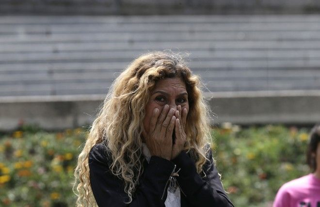 A woman reacts as people evacuate along Paseo del la Reforma Avenue after an earthquake in Mexico City, Tuesday, Sept. 19, 2017. A powerful earthquake jolted central Mexico on Tuesday, causing buildings to sway sickeningly in the capital on the anniversary of a 1985 quake that did major damage. (AP Photo/Marco Ugarte)
