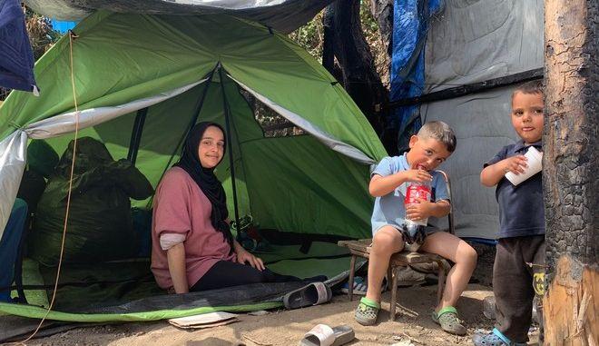 Η Σάζα με τους δύο γιους της στην σκηνή καλοκαιρινού τύπου όπου κοιμούνται στον καταυλισμό στο Βαθύ. Η φωτιά κατέστρεψε ολοσχερώς το αυτοσχέδιο κατάλυμα που είχαν φτιάξει στα τέλη Απριλίου.