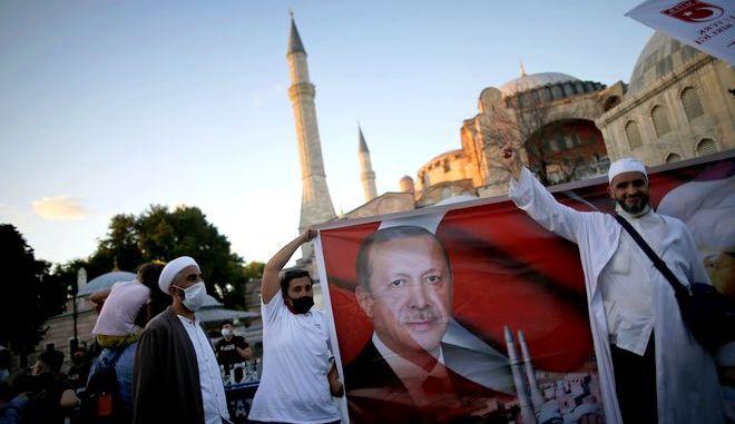 Πιστοί κρατούν αφίσα του Ερντογάν έξω από την Κωνσταντινούπολη