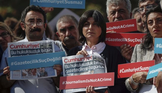 Journalists hold copies of Cumhuriyet hours before Kadri Gursel, a columnist for Cumhuriyet, Turkey's main opposition newspaper, being released from Silivri prison outside Istanbul, early Monday, Sept. 25, 2017. A court in Istanbul has ordered Gursel released from prison pending the conclusion of his trial. The court on Monday ruled that four other Cumhuriyet newspaper employees, including editor-in-chief Murat Sabuncu and investigative journalist Ahmet Sik, remain in pre-trial detention. (AP Photo/Emrah Gurel)