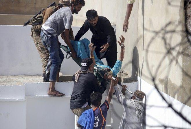 Εθελοντές απομακρύνουν τραυματία από το σημείο της συντριβής του πακιστανικού Airbus στο Καράτσι
