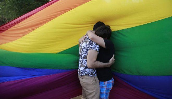 Άνθρωποι που αγκαλιάζονται μπροστά από ΛΟΑΤΚΙ σημαία