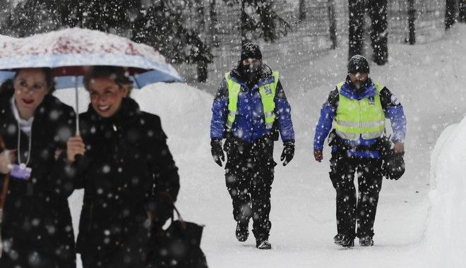 Two police officers patrol through the snow near the congress center where the World Economic Forum, WEF, will take place in Davos, Monday, Jan. 22, 2018. The meeting brings together entrepreneurs, scientists, chief executives and political leaders from Jan. 23 to 26. (AP Photo/Markus Schreiber)