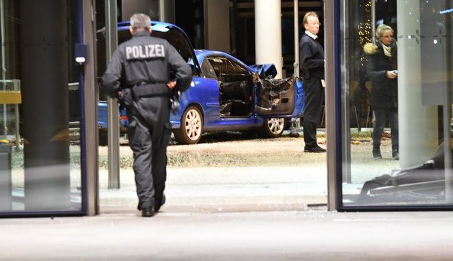 Police standing beside a damaged car in the Social Democratic party, SPD,  headquarters in Berlin, Germany, Monday, Dec. 25, 2017. Police in Berlin say a man crashed a car into the entrance area of the country's Social Democratic Party at midnight on Christmas Eve. A police statement Monday says the man described the act as a suicide attempt. A fire broke out in the car but was extinguished by the building's sprinkler system. (Paul Zinken/dpa via AP)