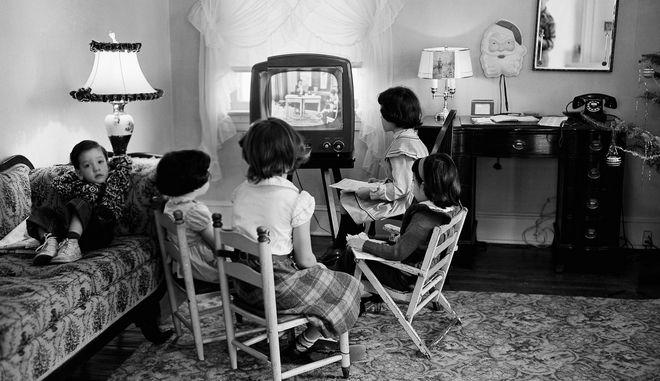 Παιδιά σχολείου παρακολουθούν  μάθημα μέσω τηλεόρασης