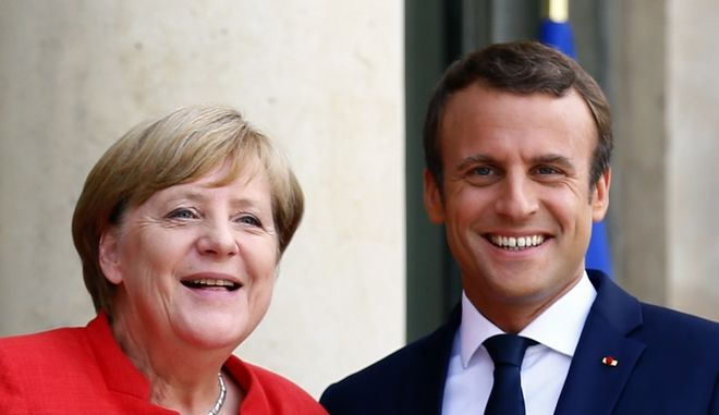 France's President Emmanuel Macron, right, poses with German Chancellor Angela Merkel prior to their meeting at the Elysee Palace, in Paris, France, Monday, Aug. 28, 2017. The leaders of France, Germany, Italy and Spain are meeting with African counterparts to find ways to curb illegal migration across the Mediterranean to European shores. (AP Photo/Francois Mori)