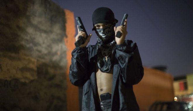 Νεαρός ποζάρει κρατώντας όπλα.