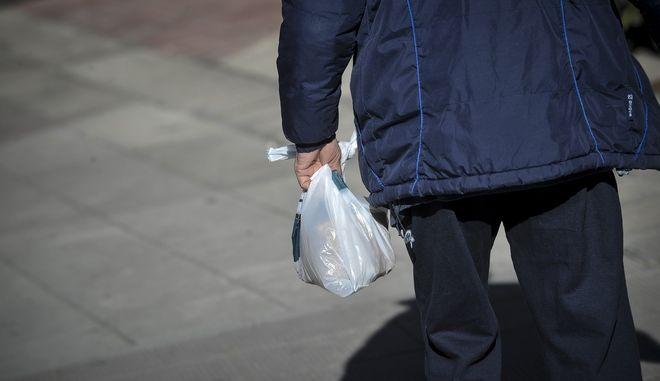 Ένας άνδρας περπατά στην πόλη των Τρικάλων  κρατώντας στα χέρια του μια πλαστική σακούλα