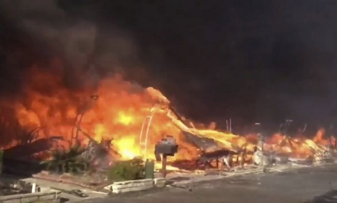 In this video grabbed image released by the San Diego Fire Department Strike Team @SDFD shows a row of homes burning in the Lilac fire in Bonsall, Calif. A brush fire driven by gusty winds that have plagued Southern California all week exploded rapidly Thursday north of San Diego, destroying dozens of trailer homes in a retirement community and killing race horses at an elite training facility. (San Diego Fire Department via AP)