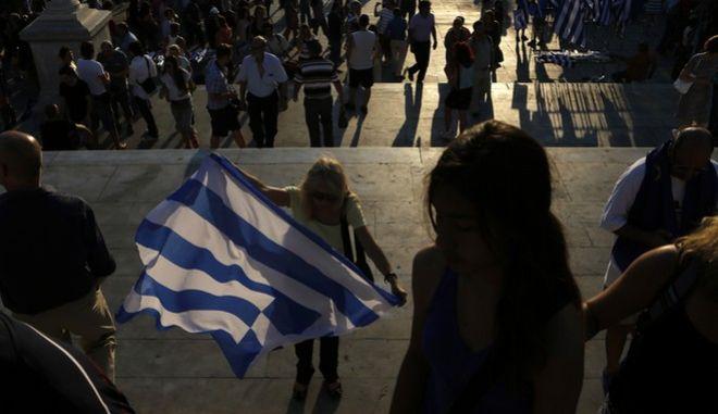 Γυναίκα στην πλατεία Συντάγματος κρατά ελληνική σημαία