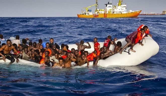 FILE - In this file photo taken on Sunday, April 17, 2016 migrants ask for help from a dinghy boat as they are approached by the SOS Mediterranee's ship Aquarius, background, off the coast of the Italian island of Lampedusa. About 340 migrants have died or gone missing in four Mediterranean Sea shipwrecks over the past two-and-a-half days during the deadliest year on record, as smugglers force departures despite rough, winter sea, a migration organization said Thursday, Nov. 17, 2016. (Patrick Bar/SOS Mediterranee via AP)