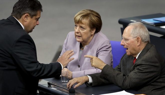From left, Vice-Chancellor and German Minister for Economic Affairs and Energy, Sigmar Gabriel, German Chancellor Angela Merkel and German Finance Minister Wolfgang Schaeuble discuss during a budget debate as part of a meeting of the German Federal Parliament, Bundestag, at the Reichstag building in Berlin, Germany, Friday, Nov. 25, 2016. (AP Photo/Michael Sohn)
