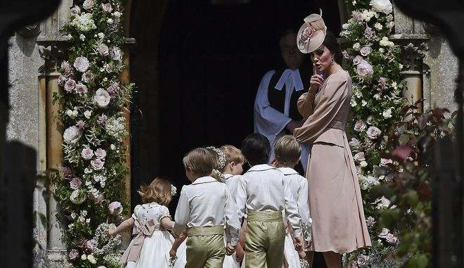 Britain's Catherine, Duchess of Cambridge, right, gestures as she walks with the bridesmaids and pageboys as they arrive for her sister Pippa Middleton's wedding to James Matthews, at St Marks Church in Englefield, England, Saturday, May 20, 2017. Middleton, the younger sister of Kate, Duchess of Cambridge is to marry hedge fund manager James Matthews in a ceremony Saturday where her niece and nephew Prince George and Princess Charlotte are in the wedding party, along with sister Kate and princes Harry and William. (Justin Tallis/Pool Photo via AP)