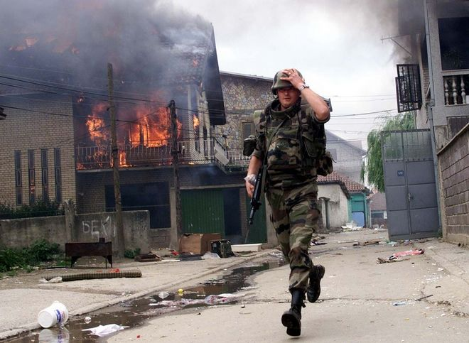 NATO French soldier holds his helmet while running past a burning house in Rasadnik, a gipsy neibourhood in Kosovska Mitrovica where some houses were set on fire Friday June, 25 1999. (AP PHOTO/Visar Kryeziu)