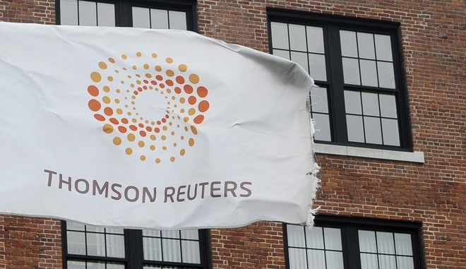 FILE-- A flag displaying the Thomson Reuters logo flies outside a company building, Monday, Aug. 11, 2008 in Boston. Reuters says it had a 30 per cent lower profit and slightly higher revenue in the first quarter compared with the same period last year. (AP Photo/Lisa Poole)