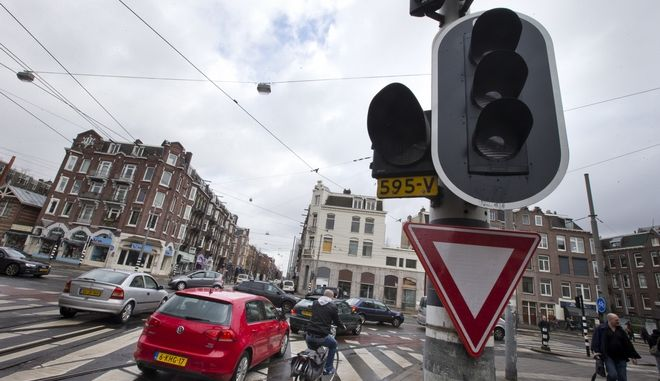 Cars and bicycles improvise crossing an intersection as traffic lights are off during a power outage in Amsterdam, Netherlands, Friday, March 27, 2015. The Dutch capital Amsterdam and surrounding towns suffered a major power outage, halting trains, trams and affecting flights to Schiphol Airport.(AP Photo/Peter Dejong)