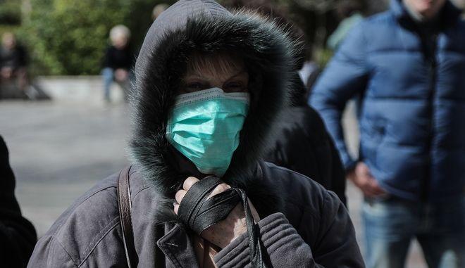 Γυναίκα κυκλοφορεί σε δρόμο της Αθήνας, φορώντας χειρουργική μάσκα